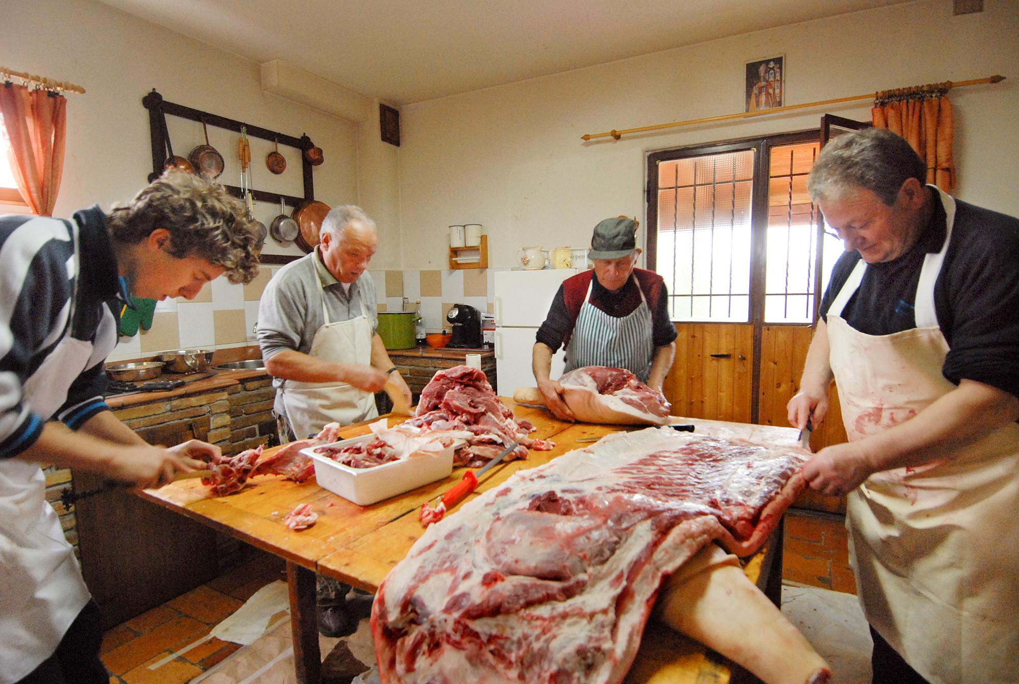 quattro persone attorno a un tavolo di legno intente a separare le varie parti del maiale macellato per ricavarne salumi e altri prodotti.
