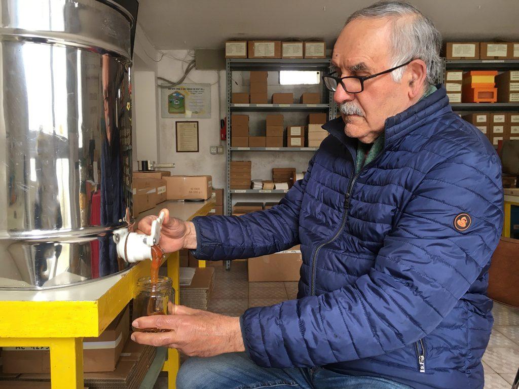 L'apicoltore Fernando versa il miele da un contenitore di metallo, in un barattolino di vetro.